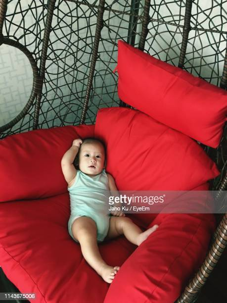 high angle portrait of cute baby boy lying on armchair at home - bucheon stock pictures, royalty-free photos & images