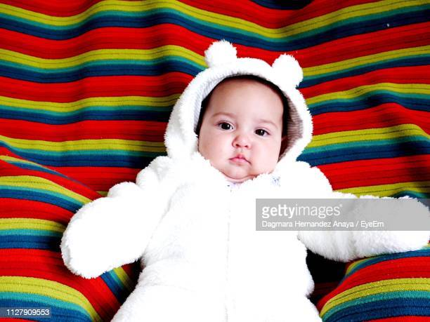 High Angle Portrait Of Cute Baby Girl Lying On Bed