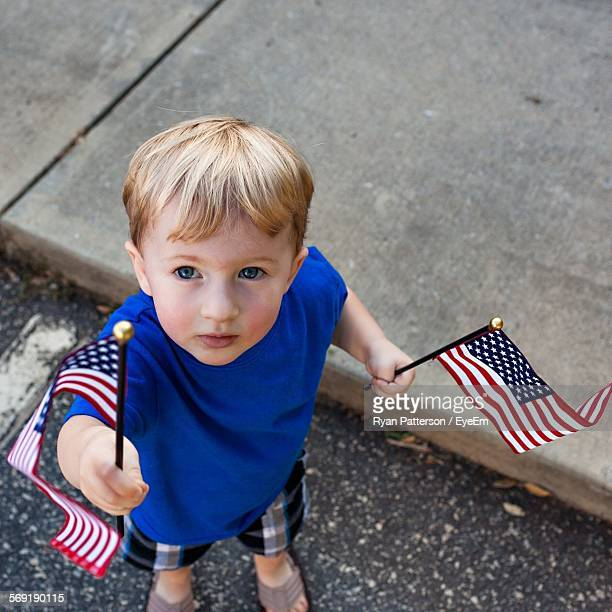 High angle portrait of cute boy holding American Flags while standing on footpath