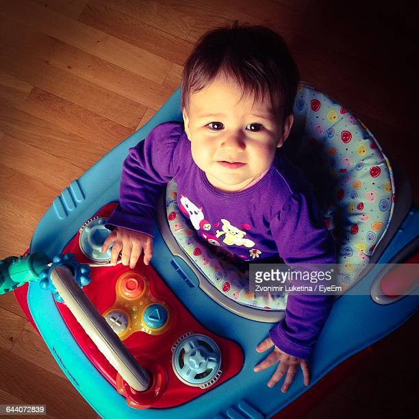 High Angle Portrait Of Cute Girl On Baby Walker At Home
