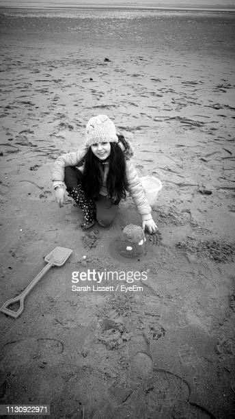 high angle portrait of cute girl wearing warm clothing playing with sand at beach - sarah sands stock pictures, royalty-free photos & images