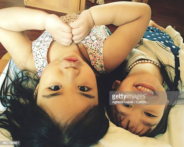 High Angle Portrait Of Cute Siblings Lying On Bed At Home