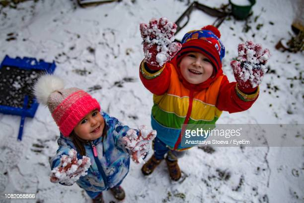 high angle portrait of cute siblings standing on snow covered field - deep snow stock pictures, royalty-free photos & images