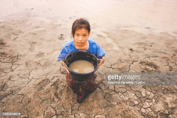 high angle portrait of girl carrying bucket of muddy water on shore at beach - drought stock pictures, royalty-free photos & images