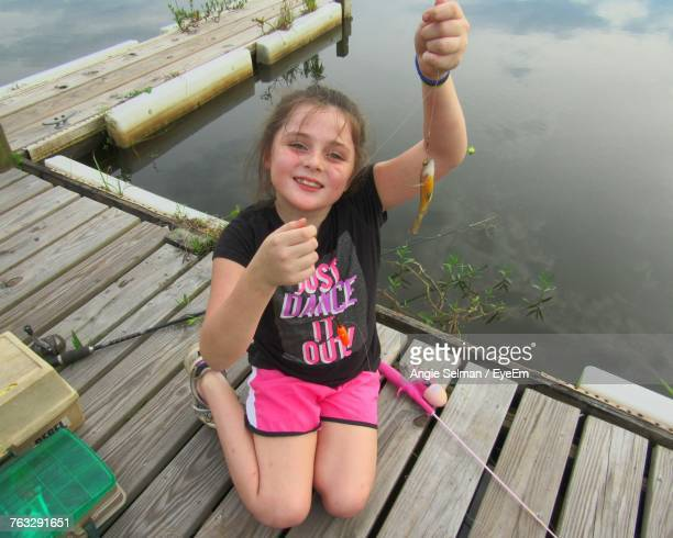 high angle portrait of girl holding fish while sitting on jetty by lake - dead girl stock pictures, royalty-free photos & images