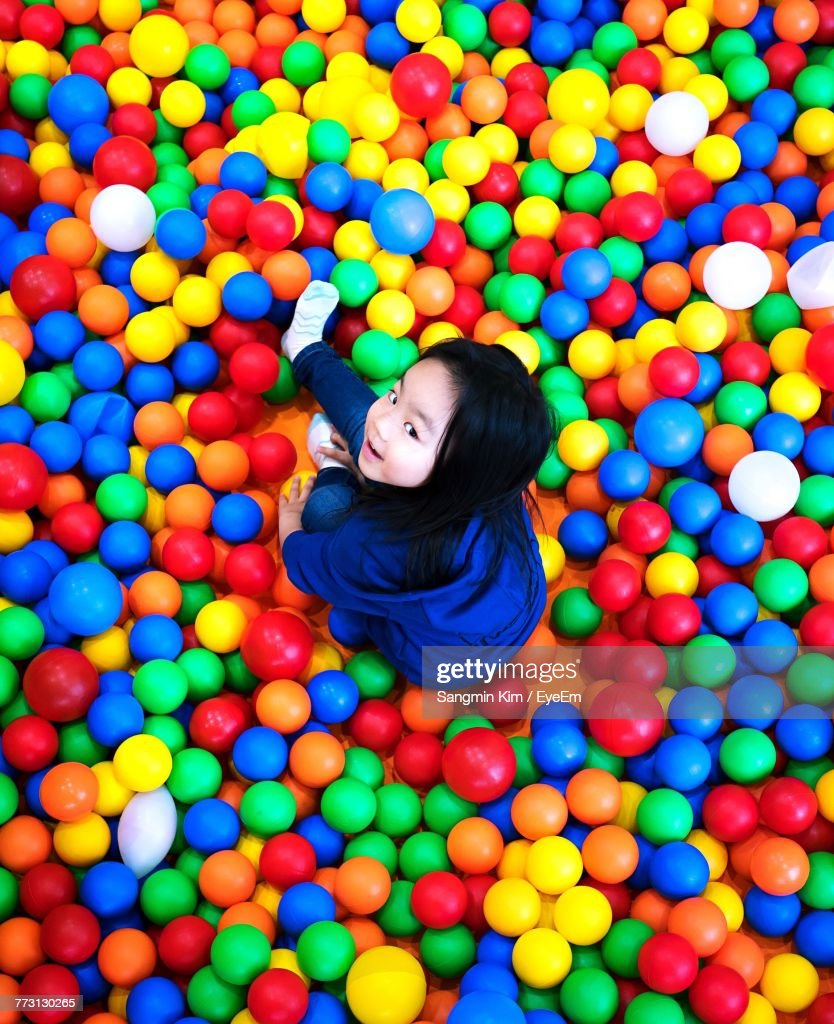 High Angle Portrait Of Girl Playing In Ball Pool : Photo
