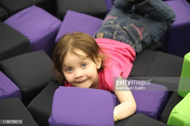 high angle portrait of girl playing on pillows - state college - fotografias e filmes do acervo