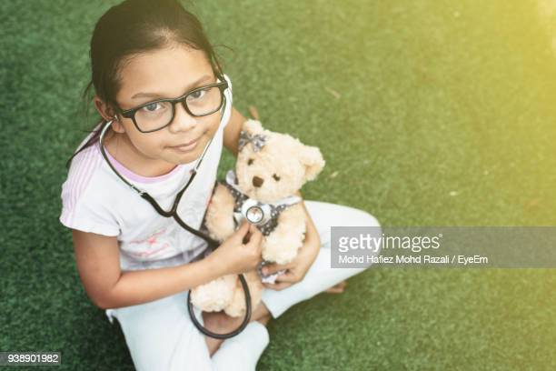 High Angle Portrait Of Girl Playing Teddy Bear In Lawn