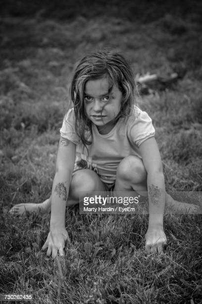 high angle portrait of girl sitting on grassy field - marty hardin stock photos and pictures