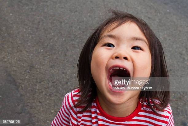 high angle portrait of girl with mouth open standing on street - girls open mouth stock-fotos und bilder