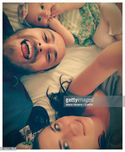 High Angle Portrait Of Happy Family On Bed At Home