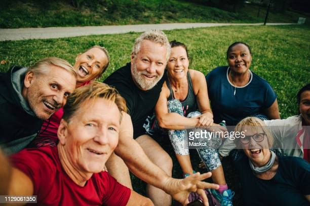 High angle portrait of happy friends taking selfie while sitting on field at park