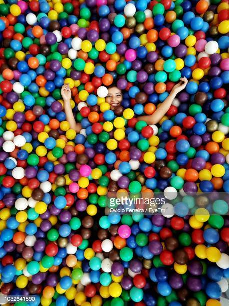high angle portrait of happy girl lying amidst colorful balls in pool - sports ball stock pictures, royalty-free photos & images