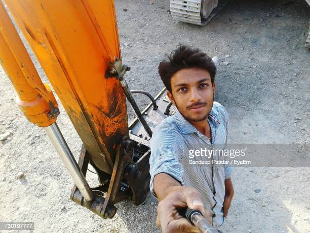 High Angle Portrait Of Man Holding Monopod While Standing By Machinery On Field