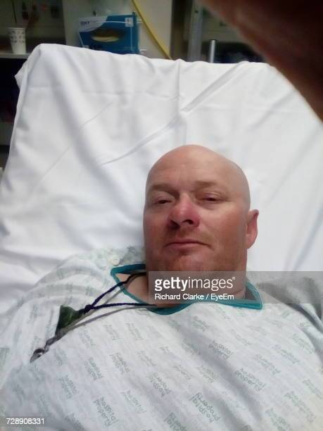 High Angle Portrait Of Man Lying On Bed At Hospital