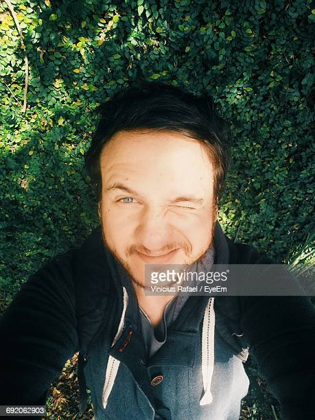 High Angle Portrait Of Man Taking Selfie While Blinking Against Plants