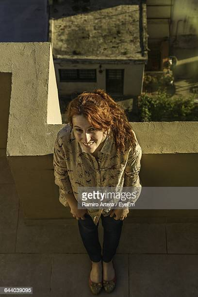 High Angle Portrait Of Redhead Woman Standing On Building Terrace