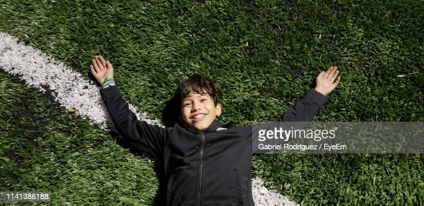 high angle portrait of smiling boy lying on soccer field - lying on back stock pictures, royalty-free photos & images
