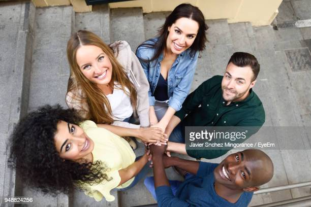High Angle Portrait Of Smiling Friends On Steps