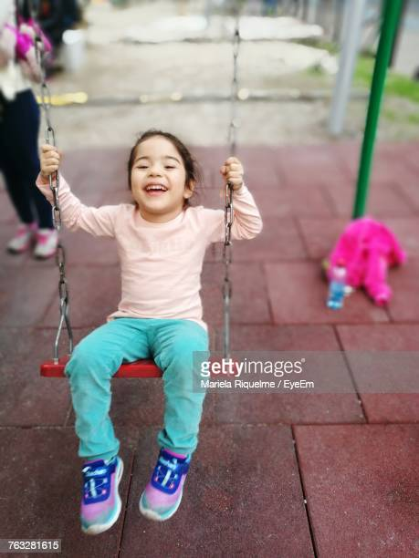 High Angle Portrait Of Smiling Girl Enjoying Swing At Playground