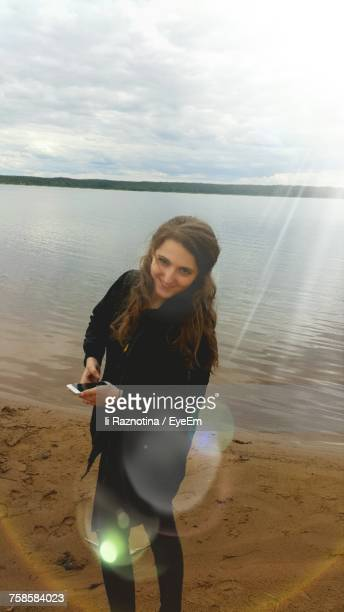 High Angle Portrait Of Smiling Woman Holding Mobile Phone While Standing At Beach Against Cloudy Sky