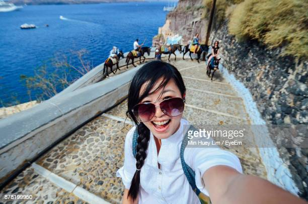 High Angle Portrait Of Smiling Woman Standing On Steps Against Sea