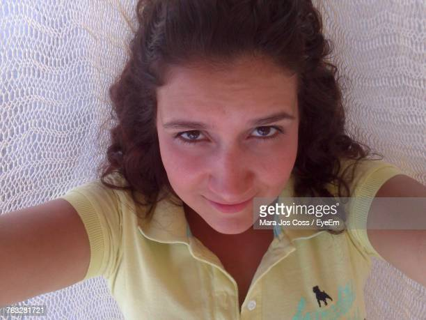 High Angle Portrait Of Smiling Young Woman Lying On Bed At Home