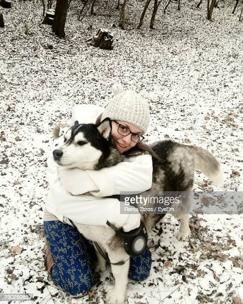 High Angle Portrait Of Teenage Girl Embracing Siberian Husky On Snowy Field In Forest