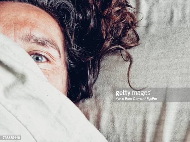 High Angle Portrait Of Woman Hiding Face With Blanket While Lying On Bed At Home