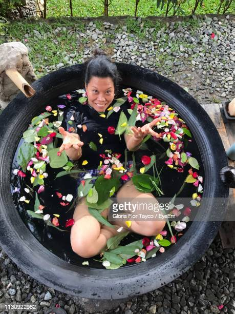 High Angle Portrait Of Woman Lying In Container With Water And Petals