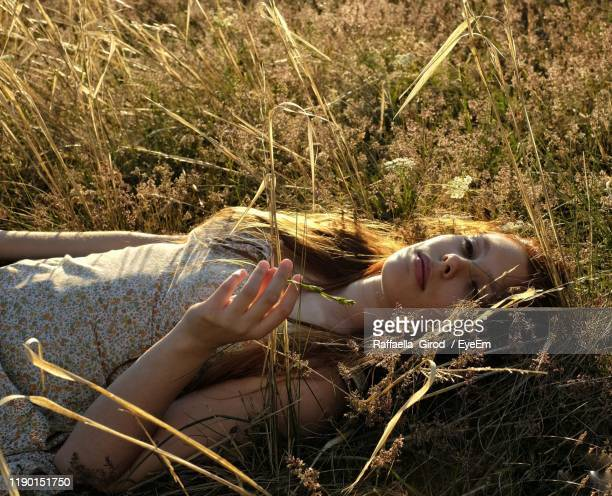 high angle portrait of woman lying on field - one young woman only stock pictures, royalty-free photos & images