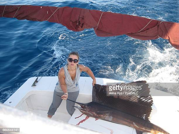 high angle portrait of woman with fish in boat sailing in sea - anna fischer stock-fotos und bilder