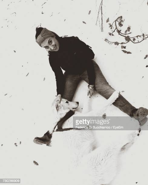 high angle portrait of woman with maremma sheepdog sitting on snowy field - pastore maremmano foto e immagini stock