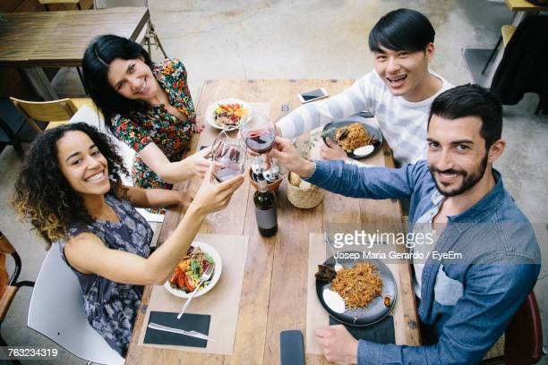 High Angle Portrait Of Young Friends Toasting Wineglasses At Restaurant