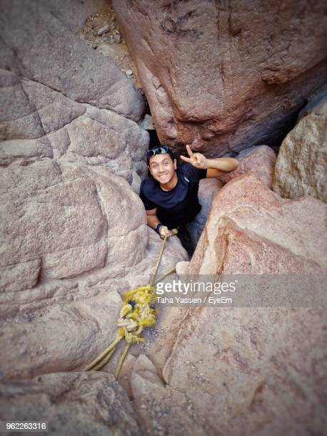 High Angle Portrait Of Young Man Gesturing Peace Sign While Standing Amidst Rocks