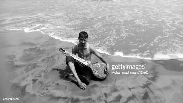 High Angle Portrait Of Young Man Playing Sitar While Sitting At Beach