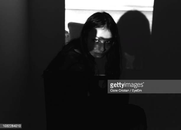 high angle portrait of young woman crouching in darkroom at home - cristian neri foto e immagini stock