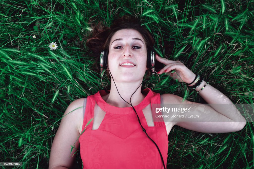 High Angle Portrait Of Young Woman Listening Music While Lying On Grassy Field : Stock Photo