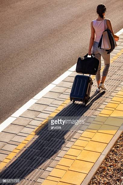 high angle rear view of a young woman walking on a sidewalk and pulling a small wheeled luggage with a briefcase on it - wheeled luggage stock photos and pictures