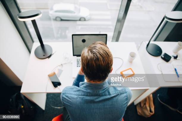 high angle rear view of businessman working at desk in office - back to work stock pictures, royalty-free photos & images