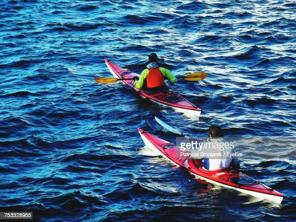High Angle Rear View Of Men Kayaking In Sea