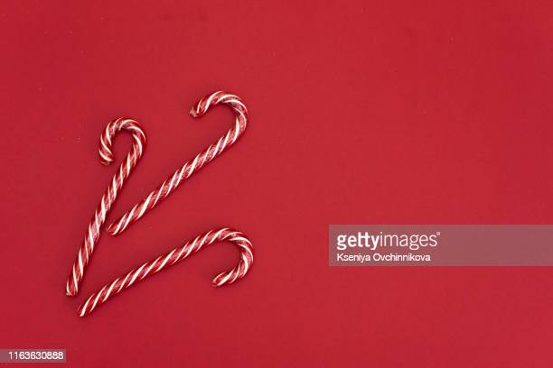 high angle shot of a group of christmas candy canes on a red background. the peppermint sticks run in all directions and out of the frame. - linda rama fotografías e imágenes de stock