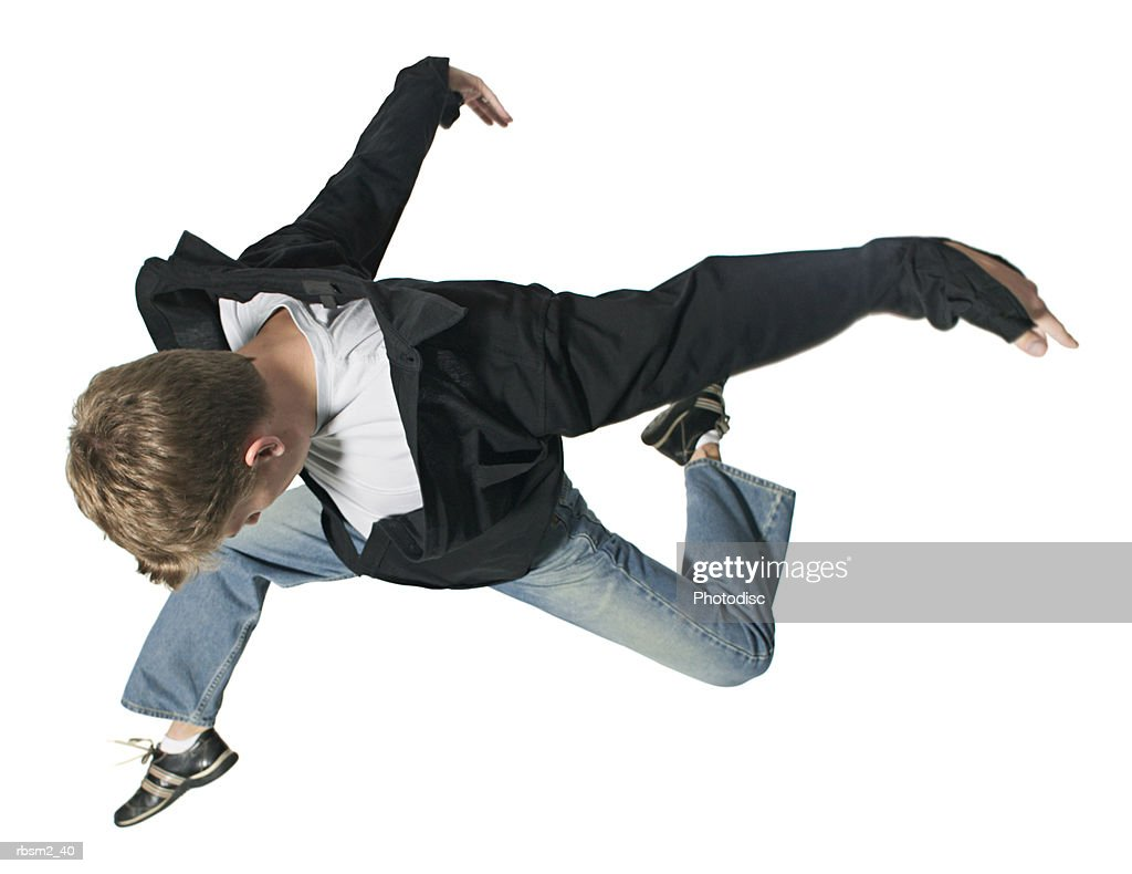 high angle shot of a young adult male in jeans and a black jacket as he jumps and flies thorugh the air : Stockfoto