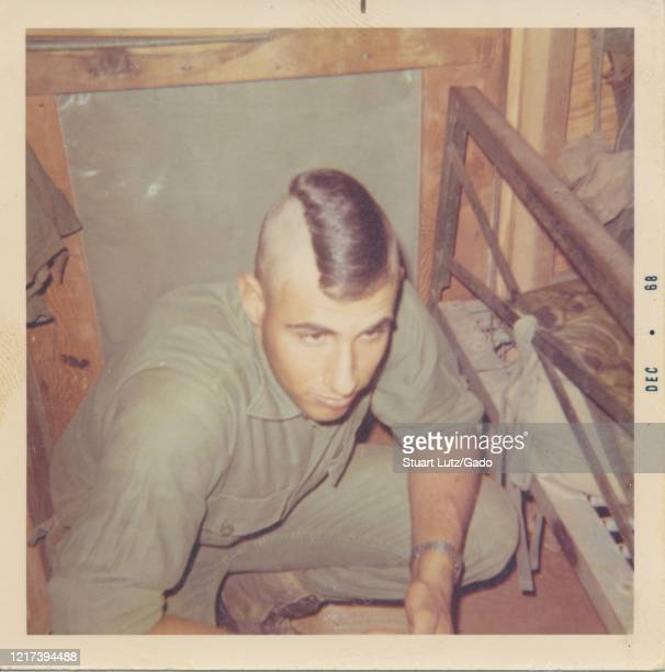 High angle shot of a young serviceman with a mohawk kneeling down near the end of a dilapidated camp bed inside a small wooden barrack, Vietnam,...