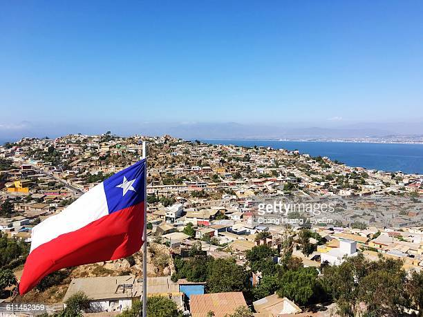 high angle shot of chile flag against townscape against blue sky - bandiera del cile foto e immagini stock