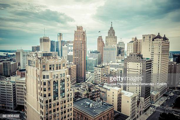 high angle shot of cityscape against clouds - detroit michigan stock-fotos und bilder