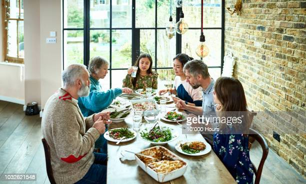 high angle shot of extended family eating dinner together - esstisch stock-fotos und bilder