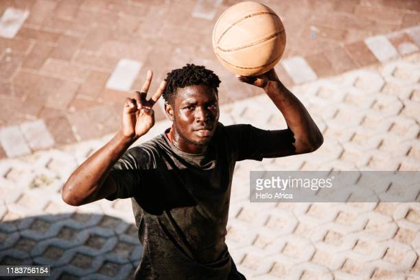 High angle shot of handsome basketball player showing Victory and holding ball