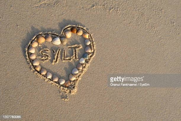 high angle shot of love letter sylt inside sand heart shape on hoernum beach on sylt island. - love island stock pictures, royalty-free photos & images