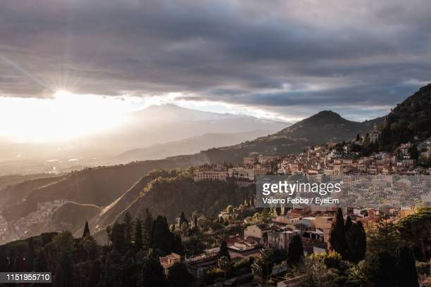 high angle shot of townscape against cloudy sky - taormina stock pictures, royalty-free photos & images